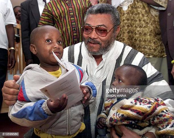 Former Ghanaian President Jerry Rawlings poses 29 September 2001 with fiveyearold Dickson Mungai and 18monthold Edel Wanjiru both HIV positive at the...
