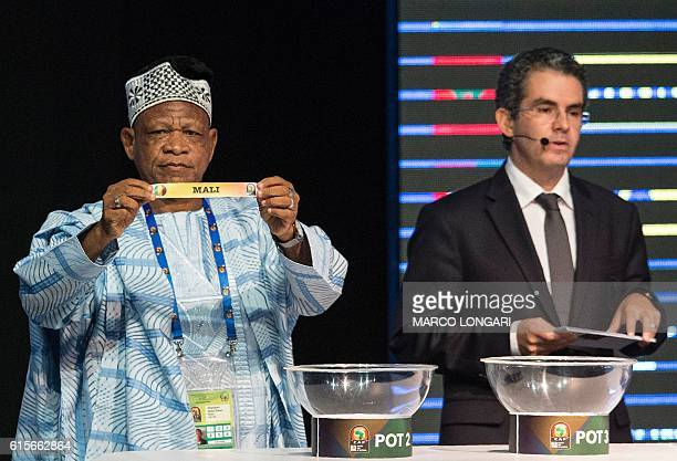 Former Ghanian soccer star Opoku Nti holds a shows a piece of paper bearing the name of Mali next to Confederation of African Football secretary...