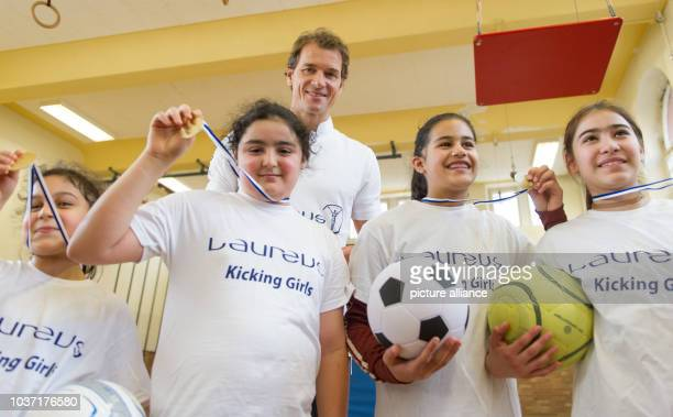 Former goalkeeper of the German national soccer team Jens Lehmann and young female pupils pose for a picture during presentation of the project...