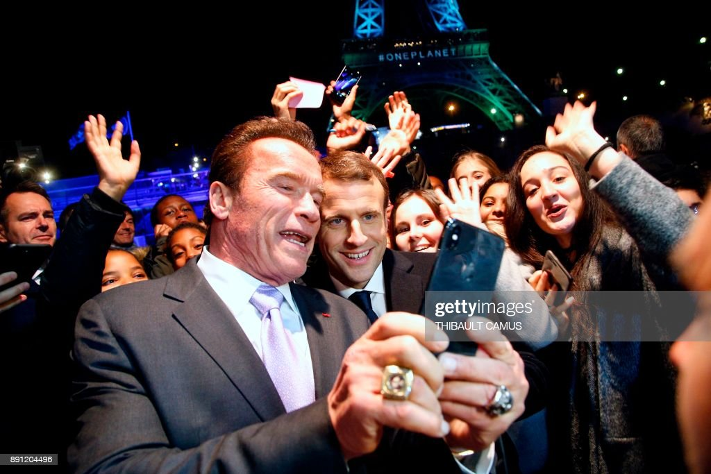 TOPSHOT - Former Governor of California and US actor Arnold Schwarzenegger (L) and French President Emmanuel Macron (C) take a selfie with youths in front of the Eiffel Tower illuminated in green, aboard a boat cruising on the river Seine, after the One Planet Summit in Paris on December 12, 2017. The French President hosts 50 world leaders for the 'One Planet Summit', hoping to jump-start the transition to a greener economy two years after the historic Paris agreement to limit climate change. / AFP PHOTO / POOL / Thibault Camus