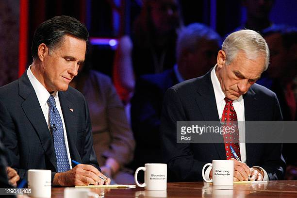 Former governor of Massachusetts Mitt Romney and US Rep Ron Paul take notes before a presidential debate hosted by Bloomberg and the Washington Post...