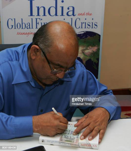 Former Governor of Reserve Bbank of India Dr YV Reddy signs on a 100 Rupees Indian currency note as a compliment to one of his young fans Monica...