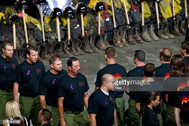 Former Granite Mountain Hotshot firefighters walk past ceremonial firefighter boots and clothing during a memorial service honoring 19 fallen...
