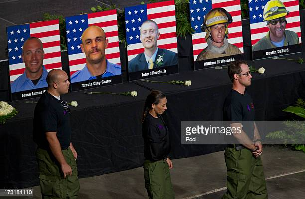 Former Granite Mountain Hotshot firefighters walk past photos of their fallen comrades during a memorial service at Tim's Toyota Center July 9 2013...