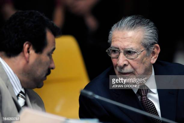 Former Guatemalan de facto President retired General Jose Efrain Rios Montt speaks with one of his lawyers during the opening of the trial on charges...