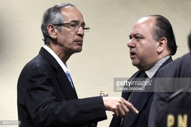Former Guatemalan president Alvaro Colom speaks with his lawyer Mario Castaneda during a court hearing in Guatemala City on February 23 2018 Colom...