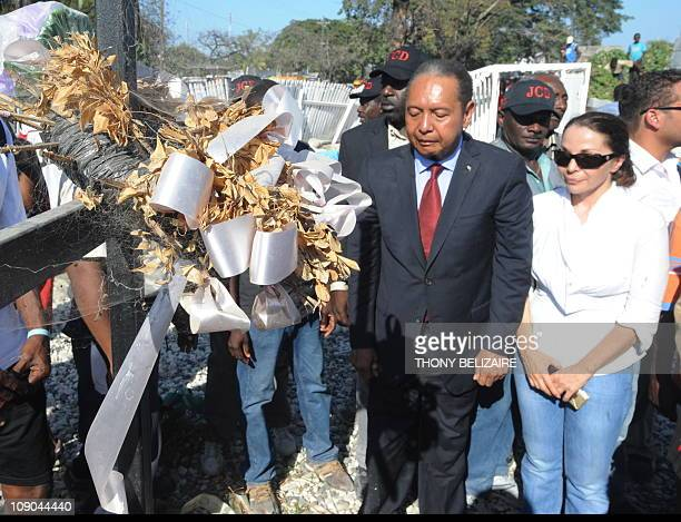 Former Haitian president JeanClaude Duvalier his partner Veronique Roy and others observe a moment of silence before the mass grave of earthquake...