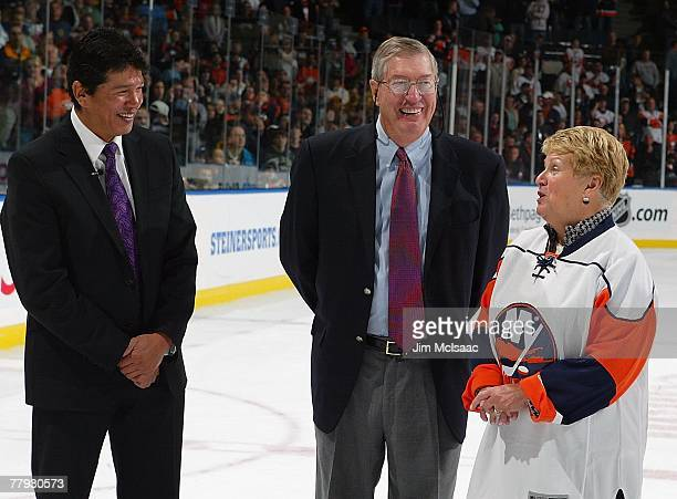 Former head coach Al Arbour of the New York Islanders stands with wife Claire and current coach Ted Nolan during post game ceremonies honoring his...
