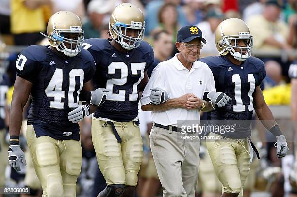 Former head coach Lou Holtz of the Notre Dame Fighting Irish walks out for the coin toss with David Grimes David Bruton and Maurice Crum prior to...