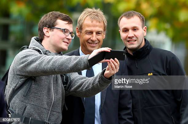 Former head coach of the German National Team Juergen Klinsmann takes a selfie with a fan prior to the ceremonial act of the 42nd DFB Bundestag at...