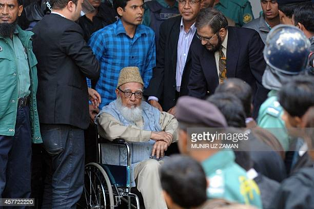 Former head of opposition JamaateIslami party Ghulam Azam escorted by security personnel and lawyers as he emerges from the Bangladesh International...