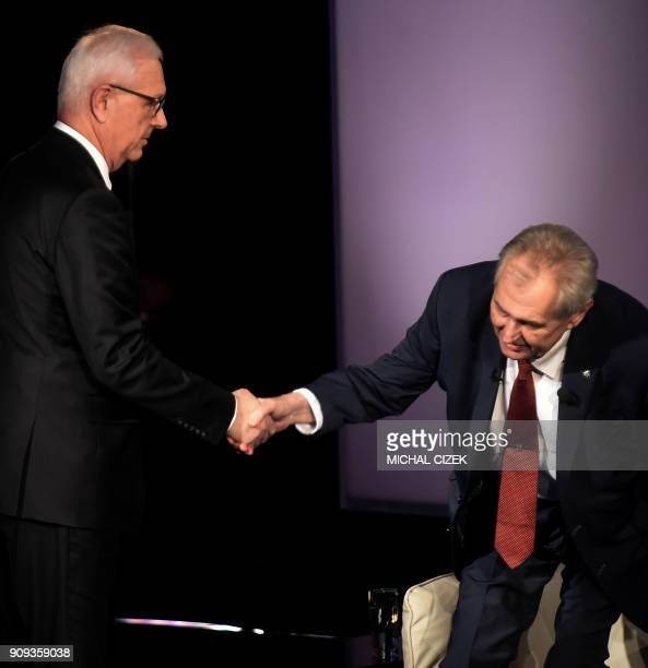 Former head of the Czech Academy of Sciences and candidate for the presidential election Jiri Drahos shakes hands with Czech President Milos Zeman as...