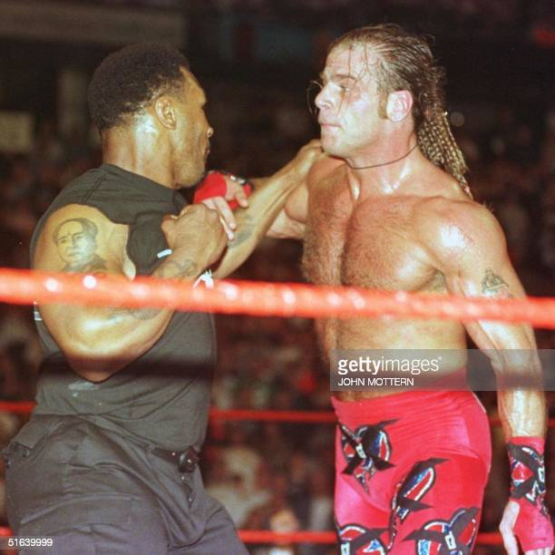 """Former Heavy Weight Boxing Champion Mike Tyson plays the role of """"Special Enforcer"""" as throws a staged punch at Shawn Michaels after the finish of..."""