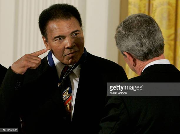 Former heavy weight boxing champion Muhammad Ali points to his head after recieving the Medal of Freedom from US President George W Bush during a...