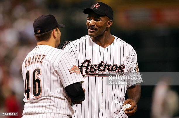 Former heavyweight boxing champion Evander Holyfield shakes hands with Raul Chavez of the Houston Astros after throwing out the first pitch before...