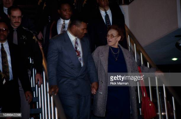 """Former heavyweight boxing champion Mike Tyson holds hands with Camille Ewald, his """"adoptive"""" mother, as they leave the courthouse."""