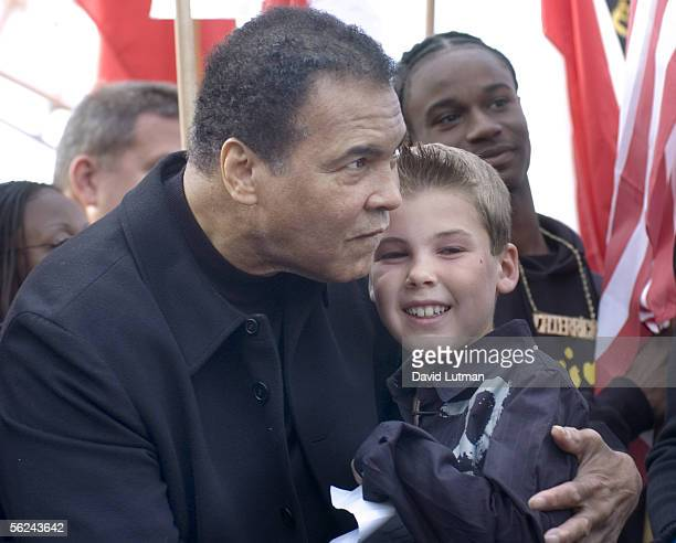 Former Heavyweight Boxing Champion Muhammad Ali hugs Mitchell Butler, a youth representative from New Zealand, after he presented a gift to Ali from...