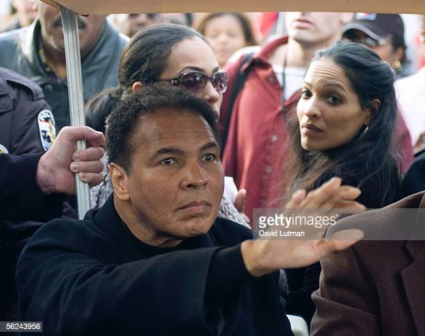 Former heavyweight boxing champion Muhammad Ali waves to the crowd as a golf cart transports him from the stage following the dedication of the...