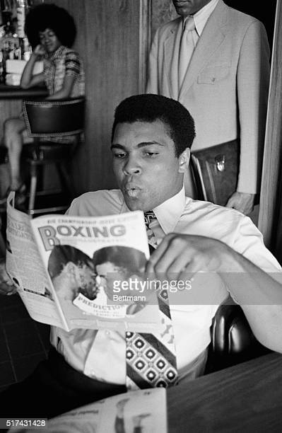Former heavyweight champion Muhammed Ali reads a boxing magazine featuring Ali and champion Joe Frazier The magazine asks when the two boxers will...