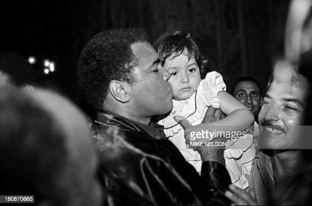 Former heavyweight world boxing champion Muhammad Ali kisses a child on October 05 1986 after praying at the Mosque of Muhammad Ali Pasha or...