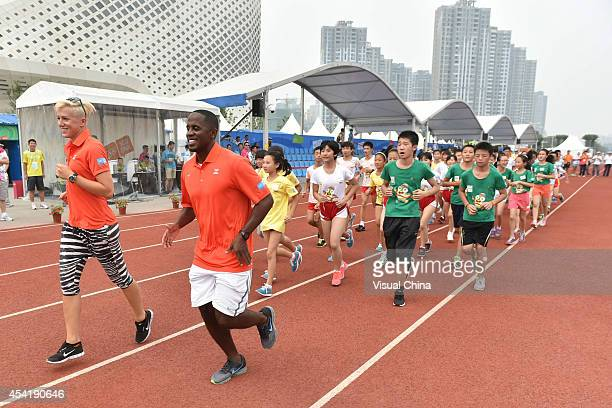 Former high jumper Kajsa Bergqvist of Sweden and World Long Jump champion Dwight Phillips of United States lead children to warm up during the IAAF...