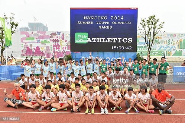 Former high jumper Kajsa Bergqvist of Sweden and World Long Jump champion Dwight Phillips of United States pose with children for a group photo...