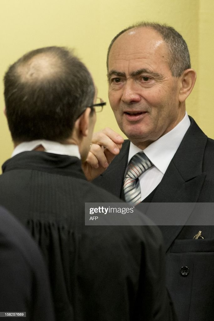 Former high-ranking Bosnian Serb general Zdravko Tolimir (C), crosses himself as he waits for the the Yugoslav war crimes tribunal to deliver its judgement and sentence for genocide charges for his role in the 1995 Srebrenica massacre in The Hague on December 12, 2012. German judge Christoph Flugge is to read his judgement and sentencing before the International Criminal Tribunal for the former Yugoslavia shortly after the hearing starts at 3:00 pm (1400 GMT) before the Hague-based tribunal with the Prosecutors asking a life sentence. AFP PHOTO / ANP / PETER DEJONG netherlands out