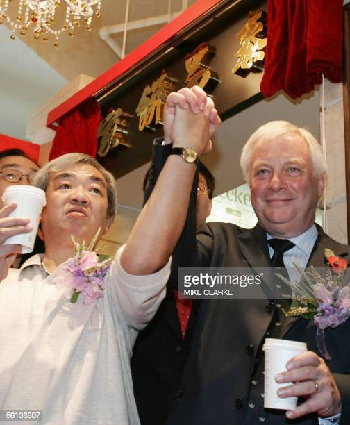 Former Hong Kong governor Chris Patten poses with bakery shop owner Au Yeung during a visit to Tai Cheung bakery in Hong Kong 11 November 2005 Patten...