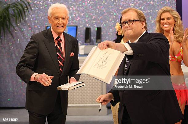 Former host Bob Barker signs an autograph for host Drew Carey during a segment of The Price Is Right at CBS Television City on March 25 2009 in Los...
