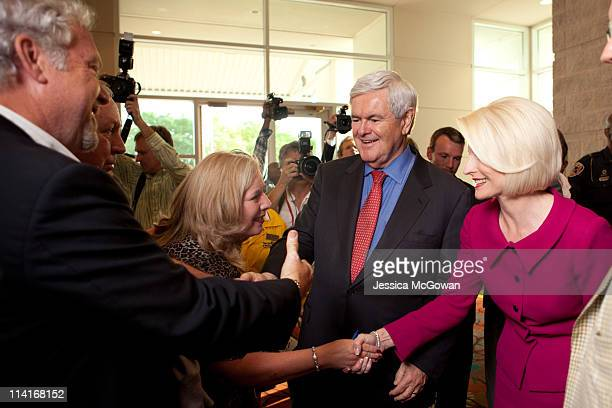 Former House Speaker Newt Gingrich and wife Calista shake hands with supporters as they enter the ballroom during the Georgia Republican Party...