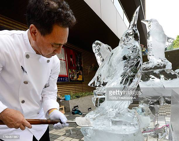Former ice carving world champion Masahiko Sasaki works on an ice sculpture of African penguins to attract summer vacationers during the heat wave in...