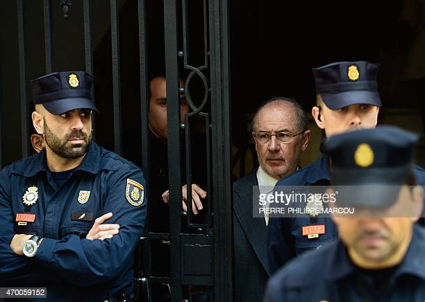 Former IMF head and former Spanish Economy minister Rodrigo Rato is surrounded by policemen as he leaves his office on April 17 2015 in Madrid...