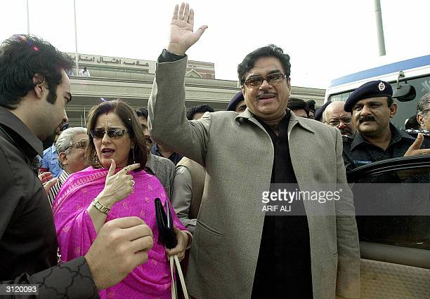 Former Indian actor turned politician Shatrungun Sinha is accompained by his wife Puneam Sinha as he waves to photographers upon his arrival at the...