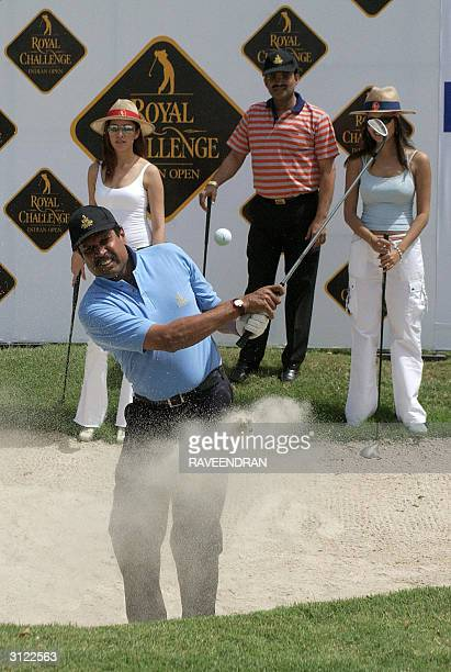 Former Indian Cricket captain Kapil Dev tees off as Indian models Aditi Govitrikar and Surthi Sharma look on during the opening day of the Royal...