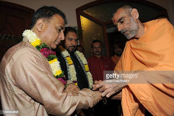 Former Indian cricketer and commentator Sunil Gavaskar is watched by colleague Arun Lal as he has aritual thread tied to his wrist by Hundu priest...