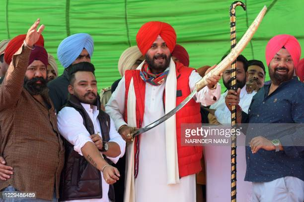Former Indian cricketer and Congress party Member of Legislative Assembly Navjot Singh Sidhu holds a sword after addressing a gathering during a...