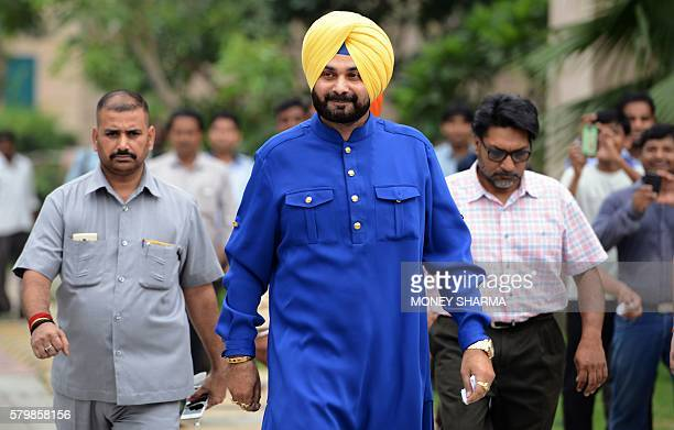 Former Indian cricketer and former member of parliament Navjot Singh Sidhu walks from his car to address the media outside his residence in New Delhi...