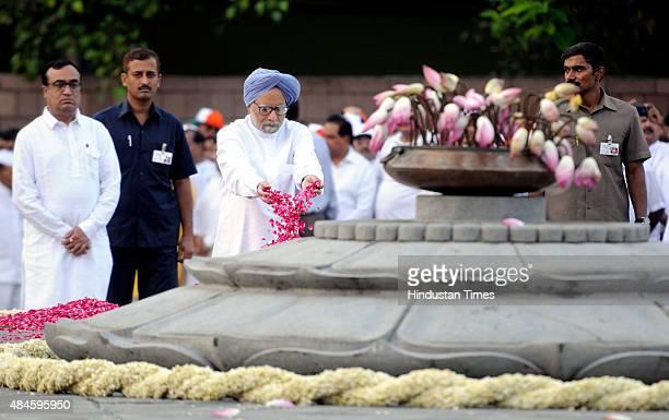 Former Indian Prime Minister Manmohan Singh pays floral tribute to the former Prime Minister Rajiv Gandhi as Congress leader Ajay Maken looks on...