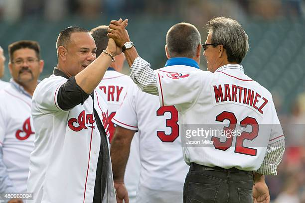 Former Indians players Carlos Baerga greets Dennis Martinez on the field prior to the game between the Cleveland Indians and the Tampa Bay Rays at...