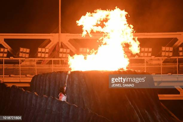 TOPSHOT Former Indonesian athlete Susi Susanti lights the cauldron during the opening ceremony of the 2018 Asian Games at the Gelora Bung Karno main...