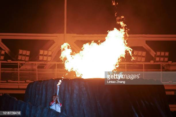 Former Indonesian athlete Susi Susanti lights the cauldron during the opening ceremony of the Asian Games on August 18 2018 in Jakarta Indonesia