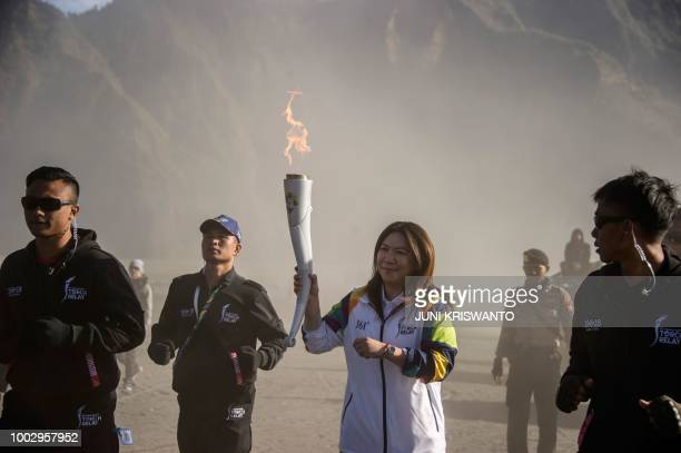 Former Indonesian badminton player Susi Susanti carries the torch for the Asian Games during the torch relay at the site of the Mount Bromo volcano...