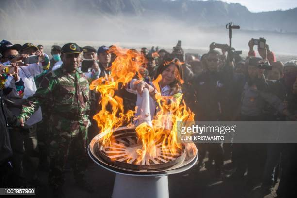 TOPSHOT Former Indonesian badminton player Susi Susanti lights the torch for the Asian Games during the torch relay at the site of the Mount Bromo...