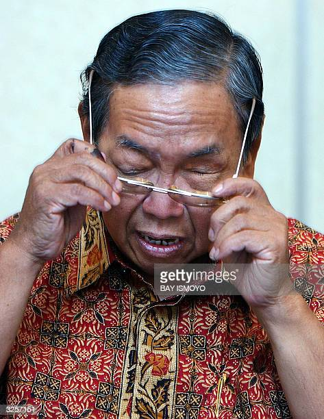 Former Indonesian president Abdurrahman Wahid wears his glasses during a press conference in Jakarta 08 April 2004 Wahid on Thursday alleged fraud in...