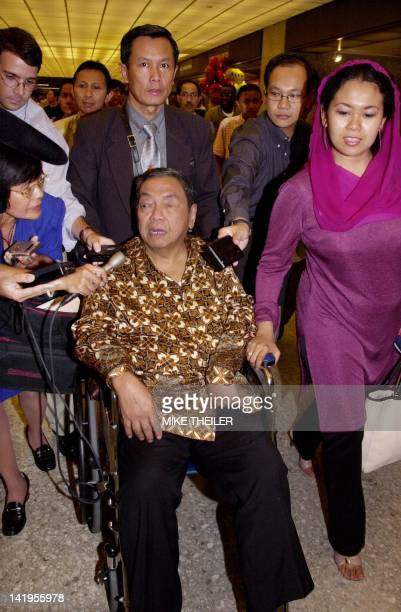Former Indonesian President Abdurrhaman Wahid is surrounded by press as he arrives at Washington's Dulles International Airport in a wheelchair after...