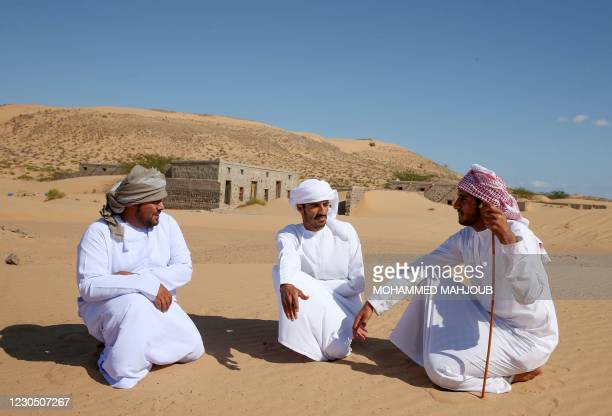 Former inhabitants of Wadi al-Murr, gather near abandoned houses in the Omani village, about 400 kms southwest of the capital Muscat, on December 31,...