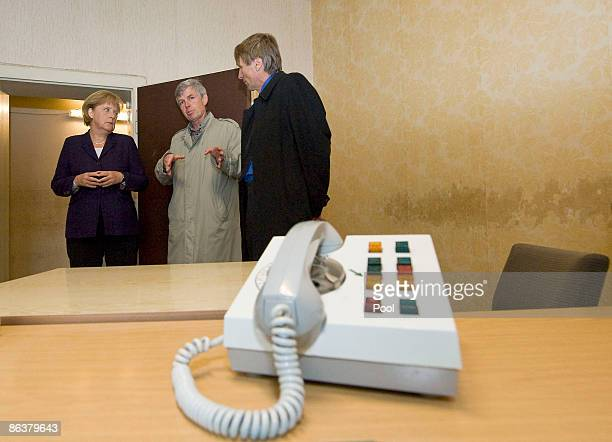 Former inmate Gilbert Furian shows German Chancellor Angela Merkel and current prison memorial director Hubertus Knabe the former prison of the East...