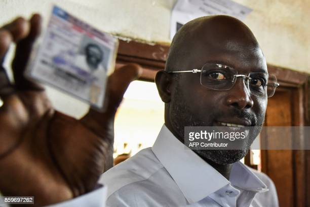 Former international Liberian football star turned politician and presidential election candidate George Weah shows his voting card prior to casting...