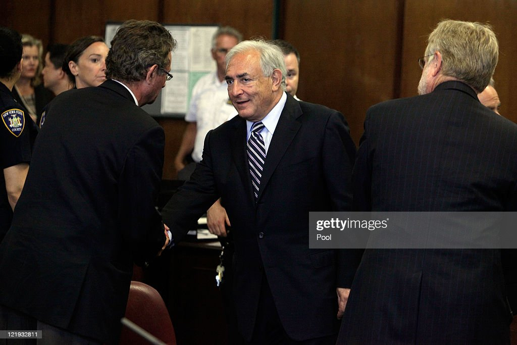 Former International Monetary Fund (IMF) director Dominique Strauss-Kahn (C) shakes hands after appearing before a judge in Manhattan district court on August 23, 2011 in New York City. A judge officially granted the Manhattan District Attorney's office motion to dismiss charges against Strauss-Kahn who was accused by Nafissatou Diallo, a hotel maid of sexual assault charges.