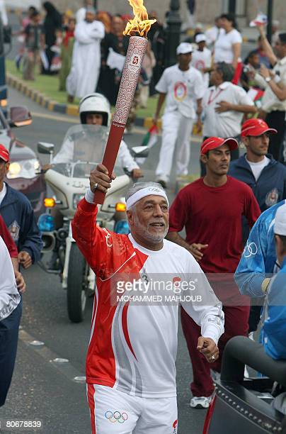 Former international tennis player Omani Majeed aLAsfour runs with the Olympic torch during its relay on April 14 2008 in Muscat The Olympic torch...